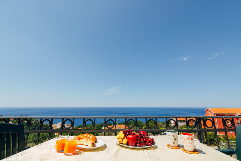 Fruits on table by sea against blue sky