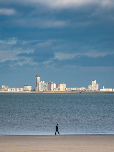 Man on beach by sea against sky in city