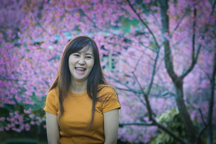 Portrait of smiling young woman with pink flower standing against trees