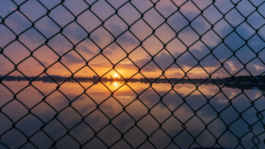 A perspective sunrise Sunrise SonyA7III Sonyalpha Bealpha Sony Landscape Landscape_Collection Landscape_photography Perspective Dawn Sunrise Water Lake Reflection Sky Cloud - Sky Chainlink Fence Dramatic Sky Storm Cloud Lightning Storm Moody Sky Thunderstorm Fence Romantic Sky Silhouette Atmospheric Mood Calm Wire Mesh Chainlink