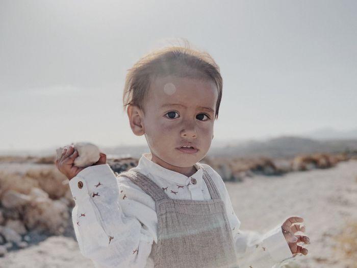 Portrait of cute boy on beach against sky