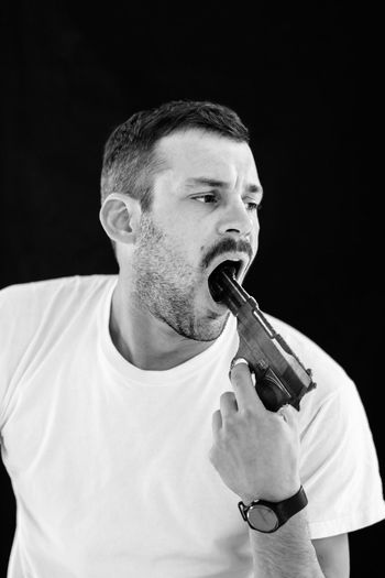 Man pointing gun in mouth against black background