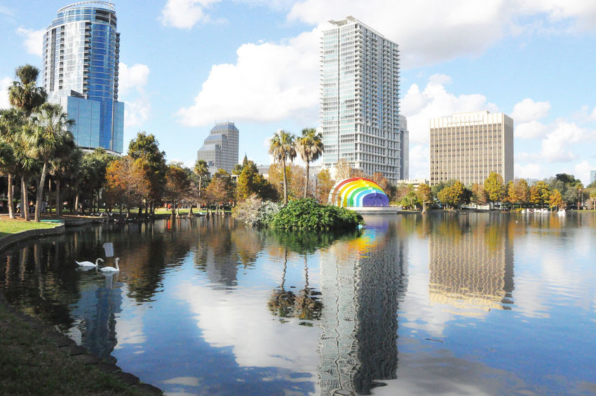 Architecture Bandshell Building Exterior Built Structure City Day Downtown District Gaypride Growth Lake Eola Park Modern Nature No People Outdoors Reflection Residential Building Sky Skyscraper Staystrong Travel Destinations Tree Urban Skyline Water