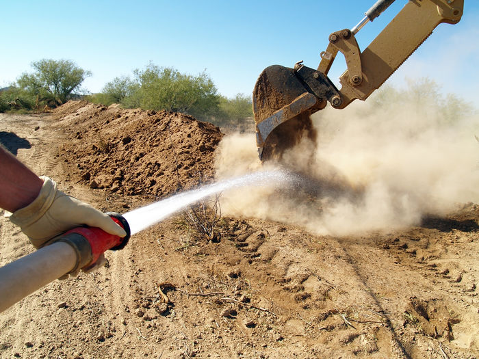 Cropped hand spraying water at construction site