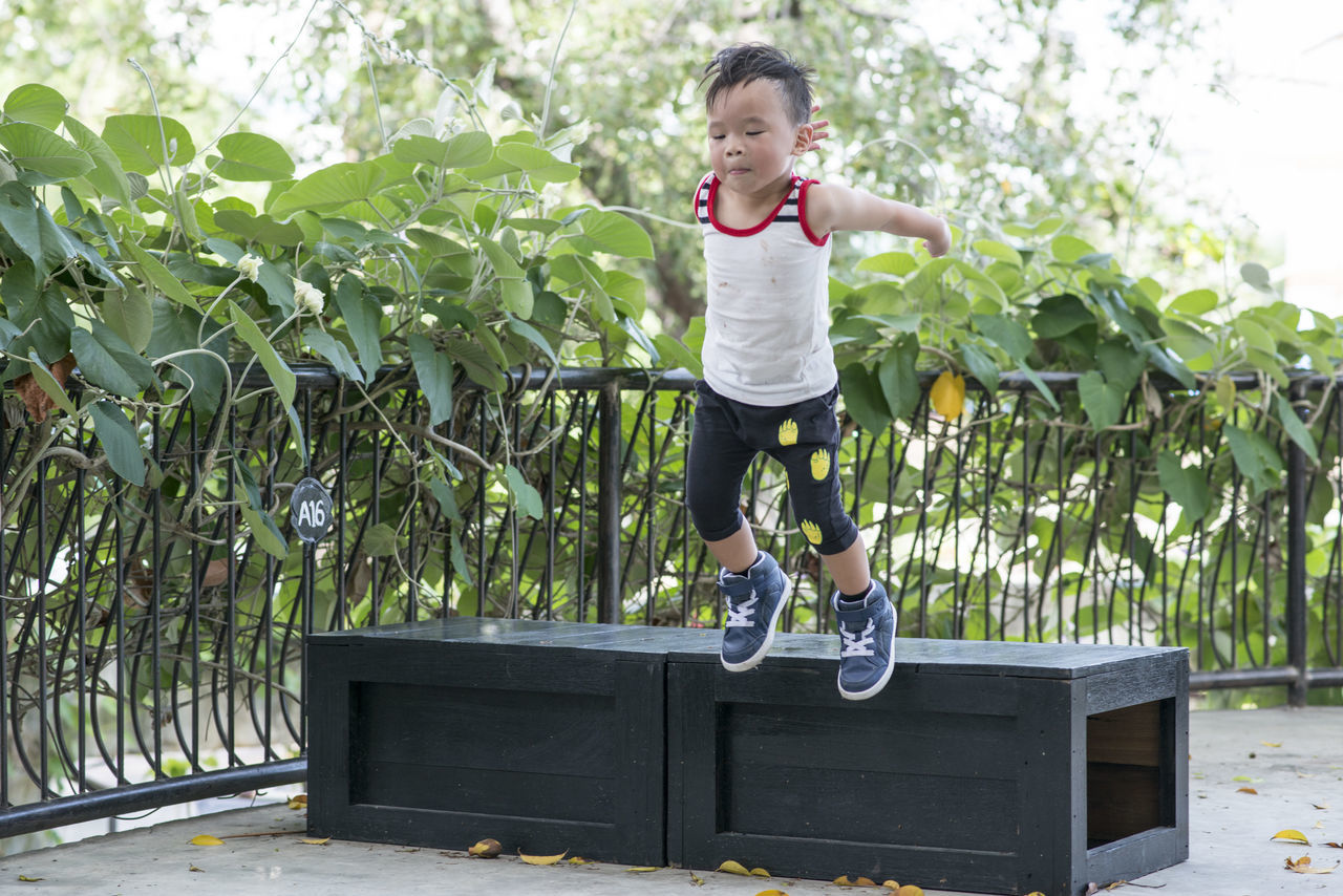 Boy Jumping From Wooden Bench Against Plants