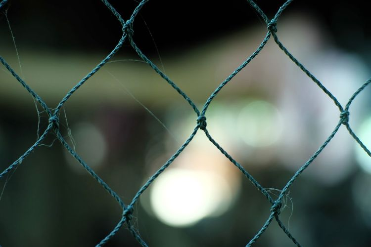 Close-up of chainlink fence against blurred background