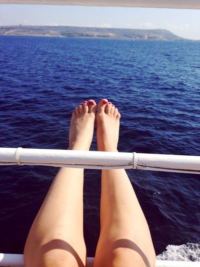 Low Section Of Woman Dangling Legs Against Sea