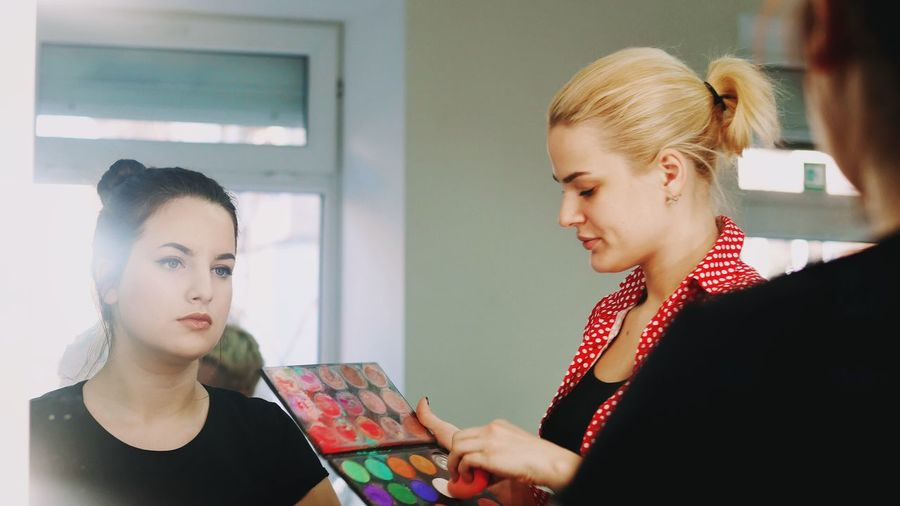 Young Women Young Adult Headshot Two People Holding Indoors  Blond Hair Women Cooperation Only Women Teamwork Technology Togetherness Working Adults Only Friendship People Day Adult Beauty Salon Makeup Businesswoman Palette Business Saloon