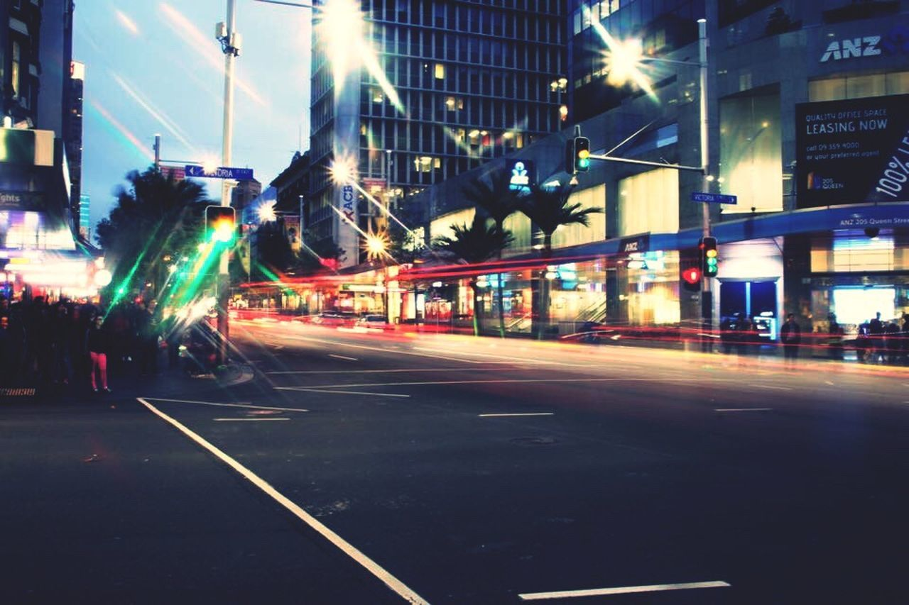 illuminated, night, light trail, motion, long exposure, blurred motion, speed, street, transportation, building exterior, architecture, city, built structure, road, high street, outdoors, street light, urban scene, no people, sky