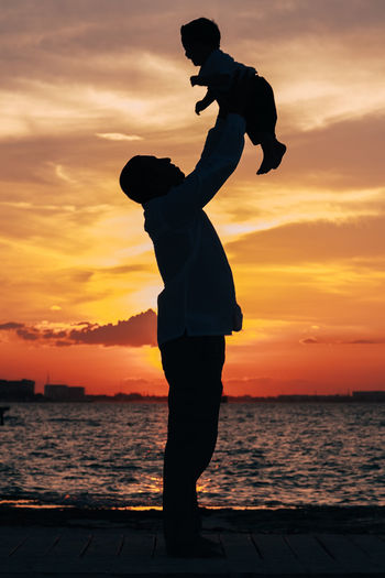 Silhouette Man Raising Son While Standing By Sea Against Sky During Sunset