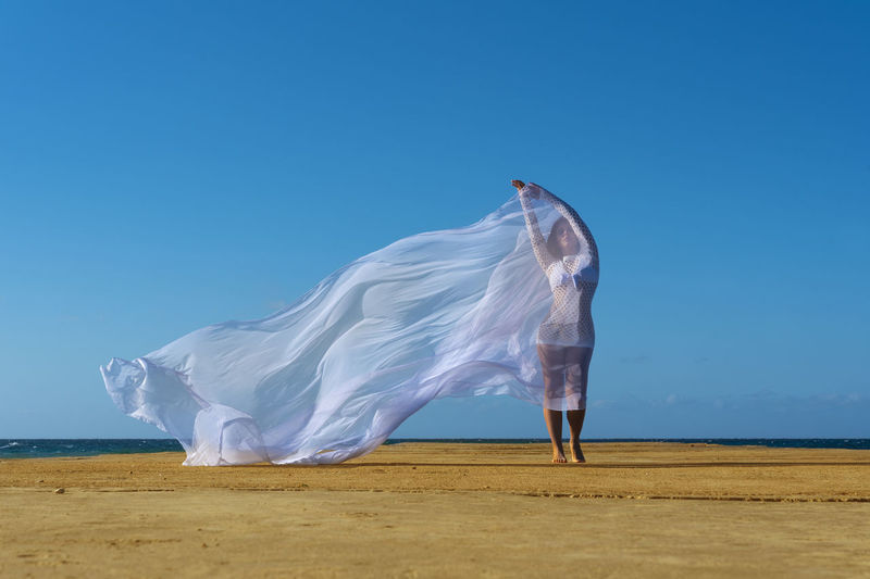 Full length of person on beach against clear sky