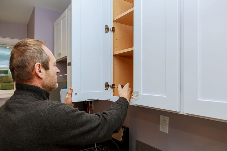Man tightening cabinet door at home