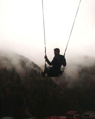 Man swinging against sky