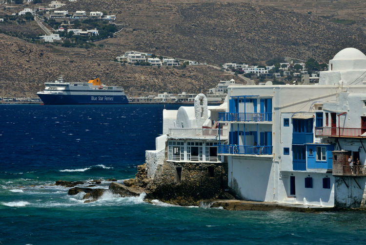 panoramic view of Little Venice in Mykonos and a ferryboat leaving the port Water Architecture Building Exterior Sea Built Structure Building Nautical Vessel Nature Land Transportation Day Mode Of Transportation Residential District Travel No People House Beach Travel Destinations City Outdoors Cruise Ship Little Venice Mykonos Mykonos,Greece Ferryboat Greek Architecture Highlights
