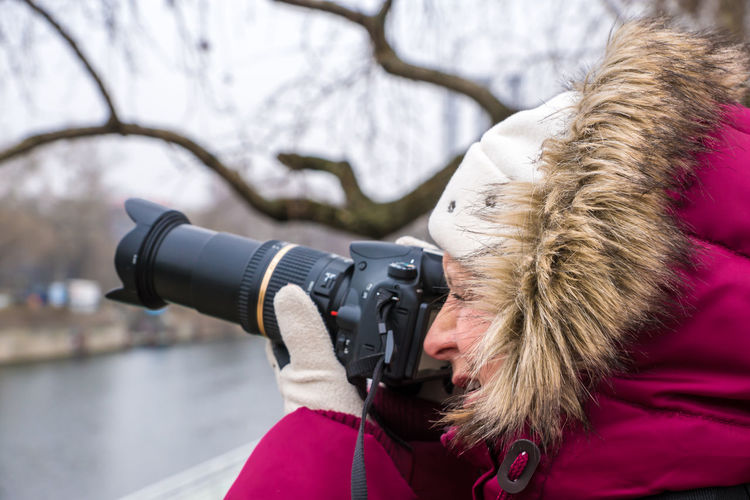 Close-up of mature woman photographing with camera during winter