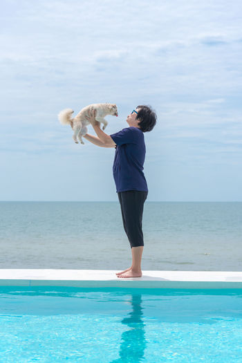 Side view of woman with dog standing against infinity pool and sky