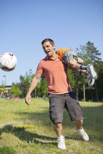 Full length of man with ball on grass against sky