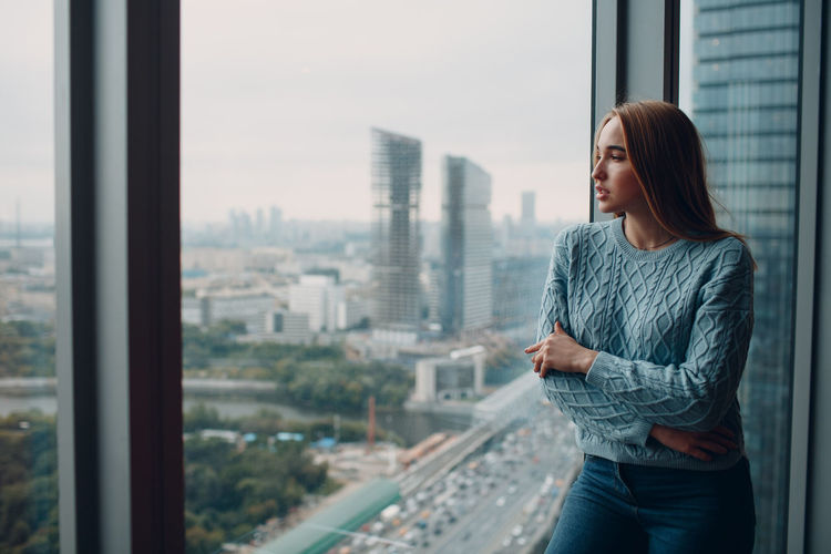 Young woman looking through glass window in city