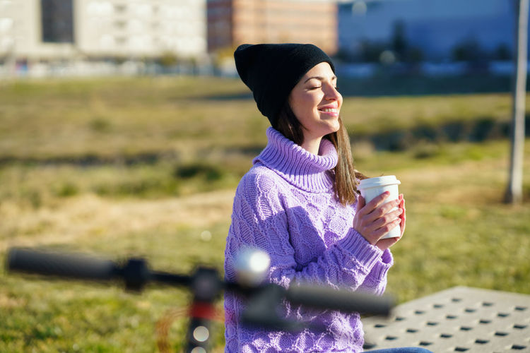 Woman holding coffee cup on field