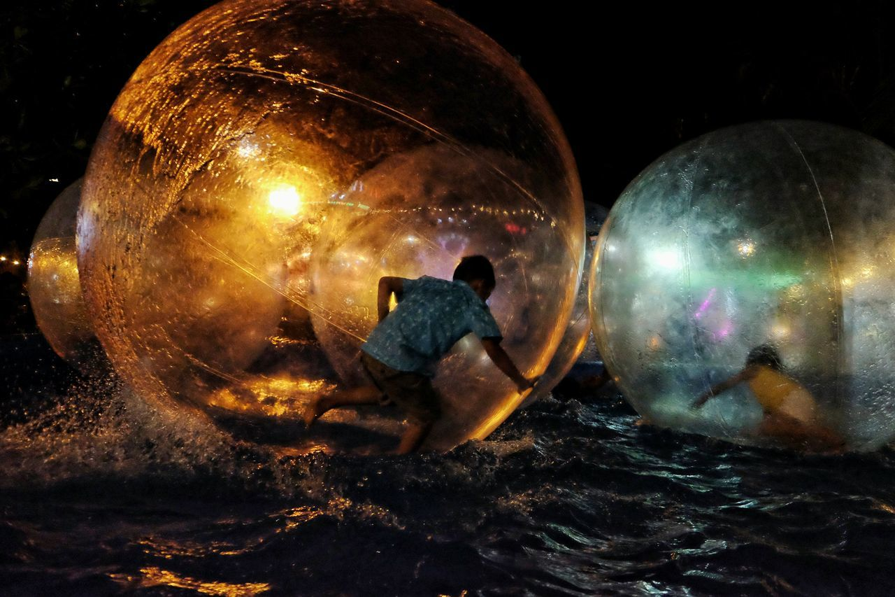 Children zorbing at lake