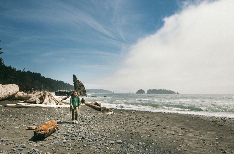 Hiker walking on shore at beach against sky at olympic national park