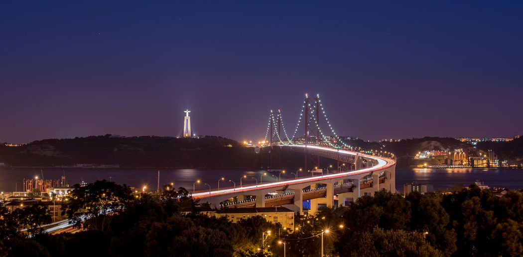 Illuminated 25 de abril bridge over tagus river by christ the king against sky at night