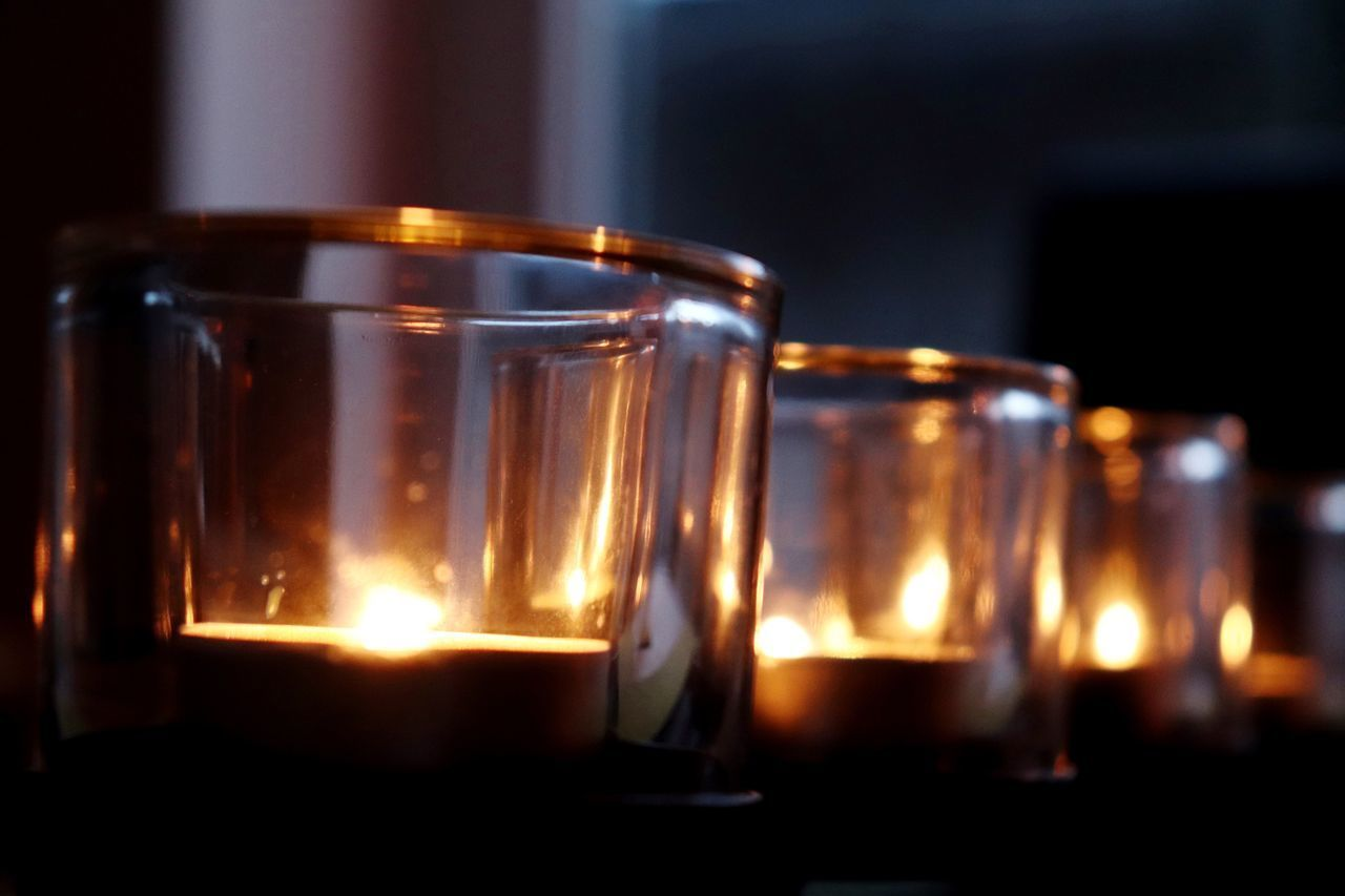 CLOSE-UP OF TEA CANDLES ON GLASS