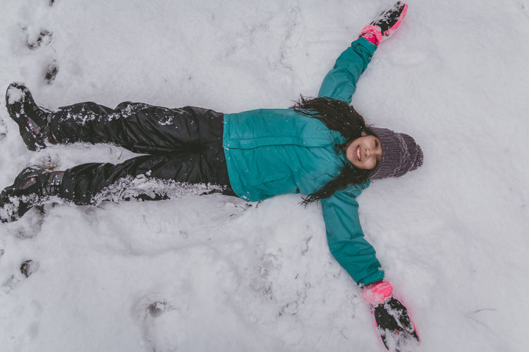 Directly above shot of girl lying down on snow