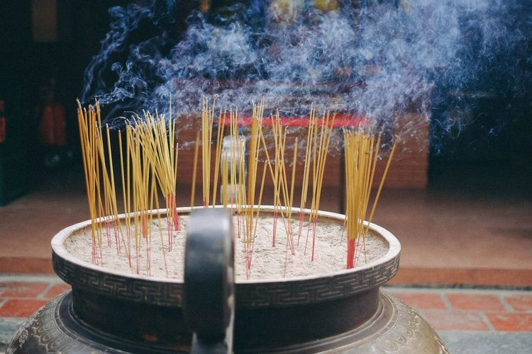 Close-Up Of Incense Sticks Burning In Container At Temple