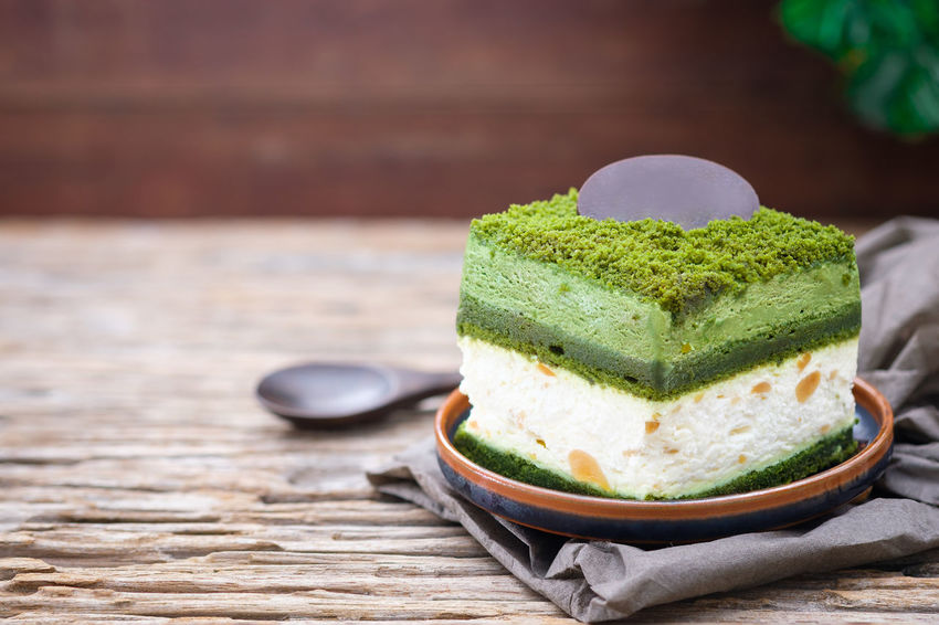 Macadamia cake with greentea and white cream on wooden table, close up, space to write. Green Color Cake Close-up Day Food Food And Drink Freshness Green Color Healthy Eating Indoors  Macadamia Matcha Tea No People Ready-to-eat Wood - Material
