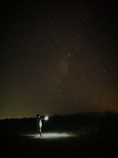 Silhouette person standing on field against sky at night