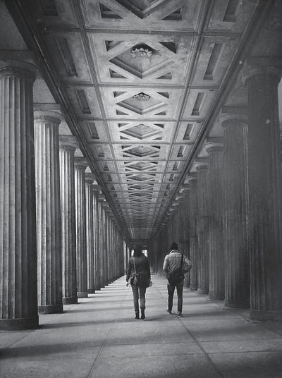 Black and white image of people walking through a gallery