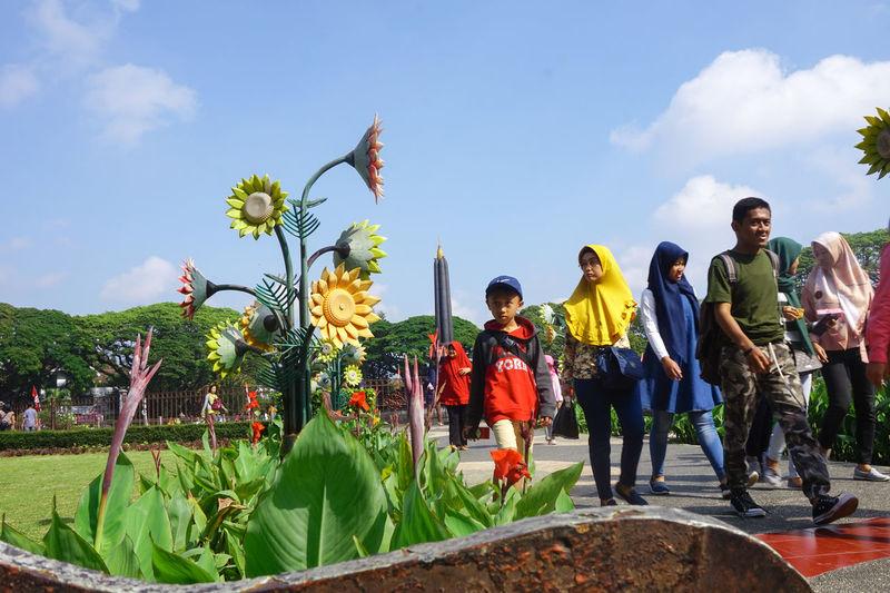 People on flowering plants against sky