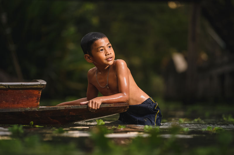 Shirtless boy holding boat in river