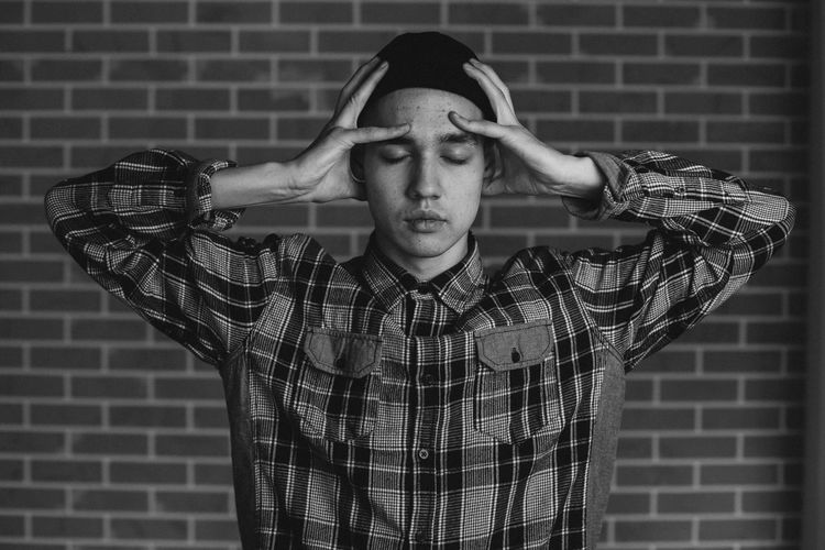 Young Man With Head In Hands Standing Against Wall