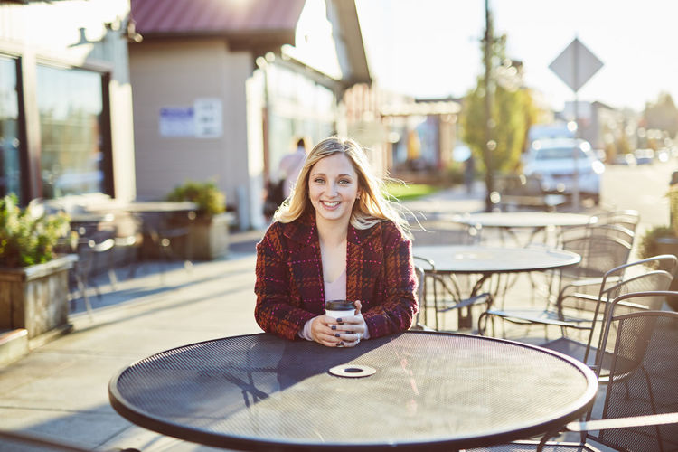 Architecture Blond Hair Building Exterior Built Structure Casual Clothing Cheerful Day Enjoyment Focus On Foreground Front View Happiness Leisure Activity Lifestyles Looking At Camera One Person Outdoors People Playing Portrait Real People Sitting Smiling Young Adult Young Women