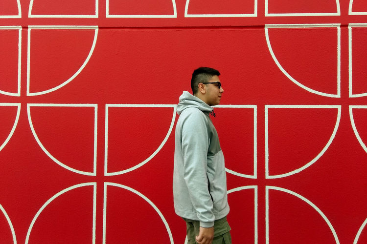 Full length portrait of man standing against red wall
