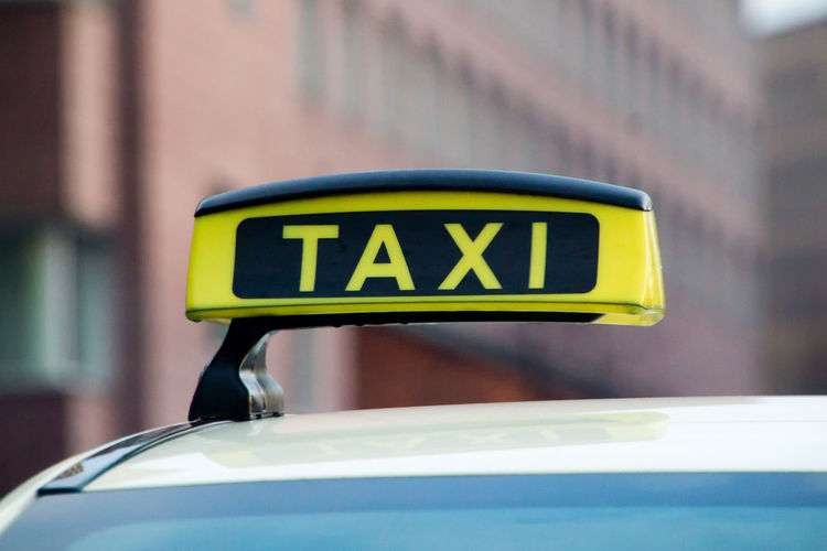 Close-up of taxi sign against building