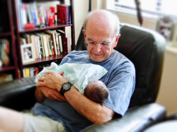 High Angle View Of Grandfather Holding Baby While Sitting On Chair At Home