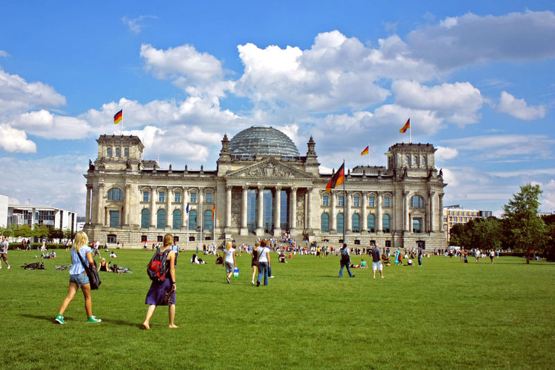 People At Reichstag Building Against Sky