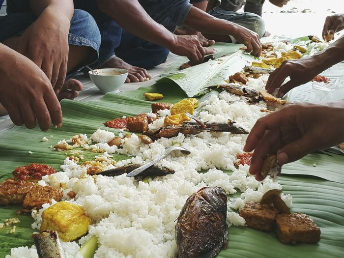 Cropped image of people eating food on banana leaves