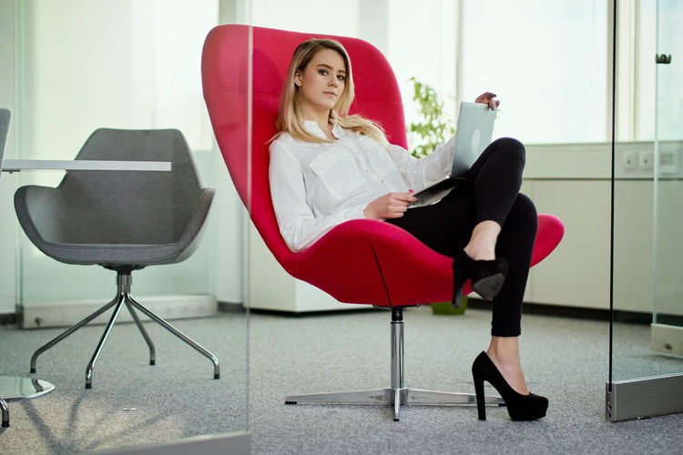 Young businesswoman sitting on red chair at office