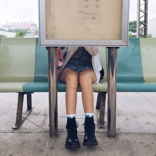 Low section of woman sitting at bus stop