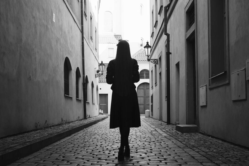 Woman Standing On Cobblestone Street