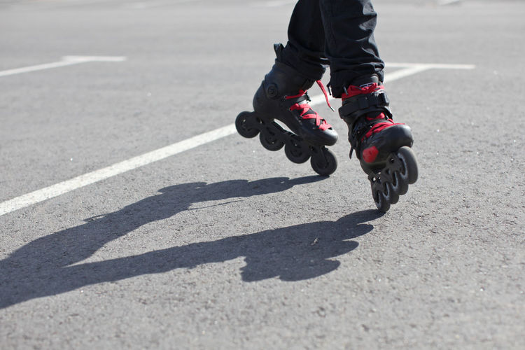 Low Section Of Person Roller Skating On Road