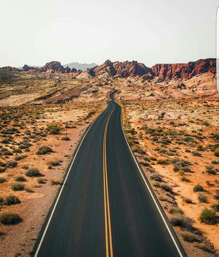 Empty Road Leading Towards Rocky Mountains Against Sky