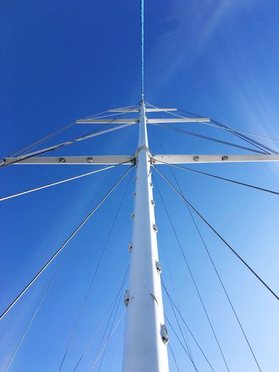 Low angle view of sailboat mast against blue sky