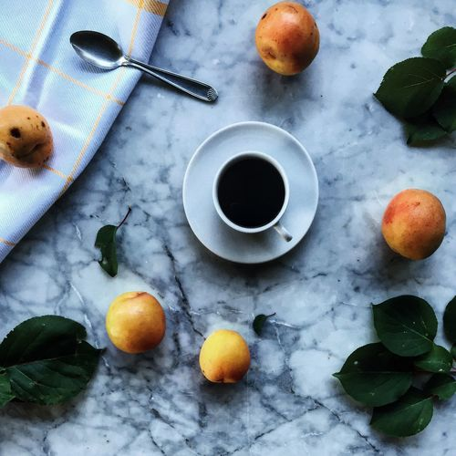 High angle view of black tea and apples