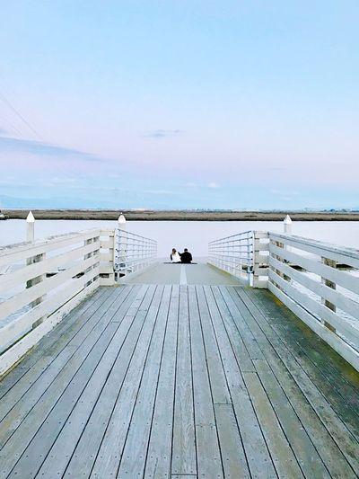 Couple Sitting On Footbridge Against Lake