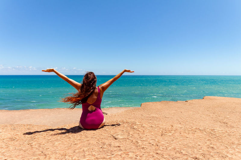 Rear view of woman sitting at beach against sky